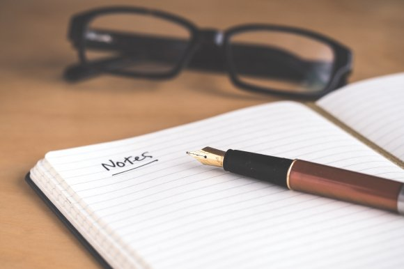 image of glasses pen and notebook symbolising meeting and taking notes