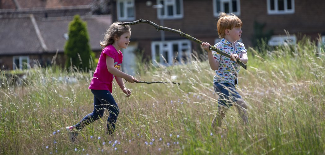 Photo of 2 children carrying sticks playing in the long grass of the wildflower meadow