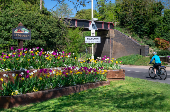 Redbourn sign in a raised bed of tulips and old railway bridge at the St Albans Road entrance to the village with cyclist to the right