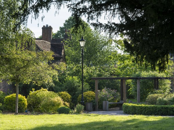 Photo of Cumberland Garden Pergola with black Victorian lamp post, hedges, shrubs and trees framing the shot